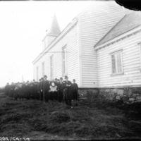 Begravelse. Begravelsefølge m/kisten går langs kirken.  K.K. Kleppe er med og bærer kisten. Dette er Klepp kirkegard.