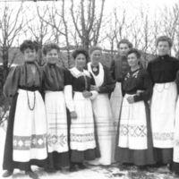 Åtte kvinnelige elever fra Jæren Folkehøg-  skule - i hagen til K.K. Kleppe.Alle i hvite pynteforklær.